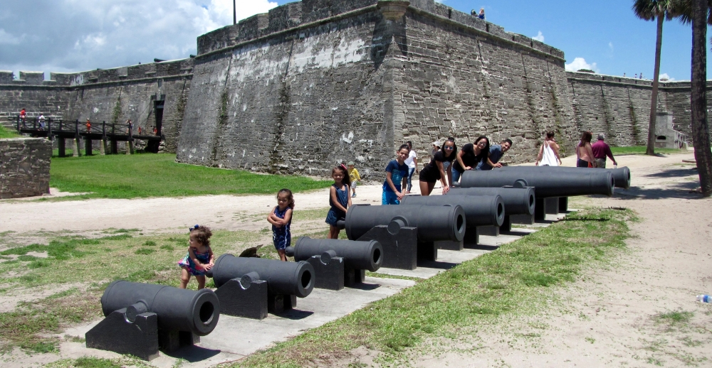 siblings posing next to canons all in a row