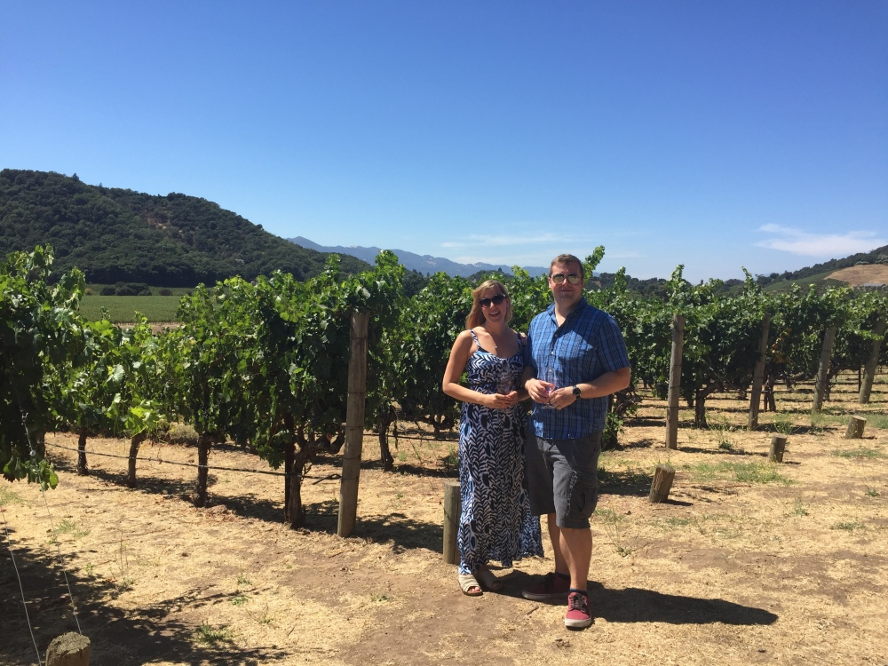newlyweds posing by vineyard in Napa